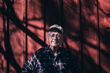 An older man in a flannel shirt near a red barn wall.