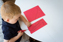 child cutting construction paper