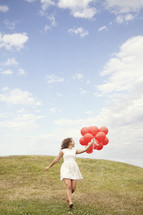 girl running with red balloons