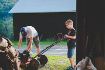 grandfather and grandson fixing a lawnmower