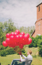 a man holding a bunch of red balloons in front of a church