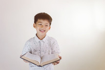 smiling boy holding a Bible