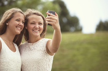 two girls taking a selfie with a cell phone.