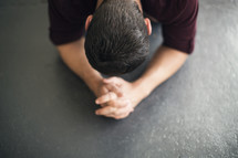 man on the ground in prayer.