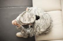 Female soldier in uniform in prayer.