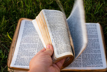turning the pages of a Bible lying on grass