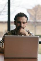 man watching sermons on a laptop