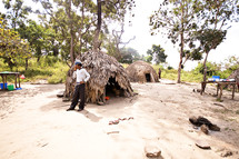 man standing next to thatched huts