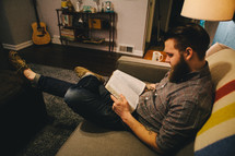 A man sitting on a couch in his living room reading a Bible.