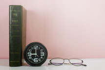 Bible spine, clock, and reading glasses