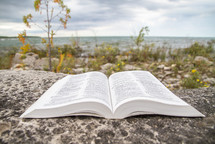 Open Bible on a rock with a coastline in the background
