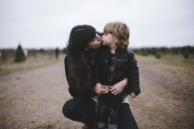 a mother kissing her son in a Christmas tree lot
