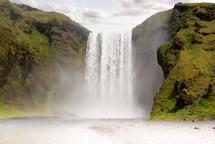 waterfall over green cliffs