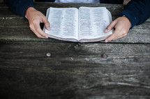 hands of a man reading a Bible at a picnic table