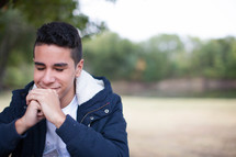 teen boy smiling with praying hands outdoors