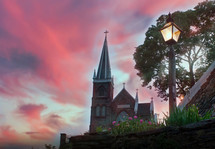 church with steeple under pink clouds at sunset