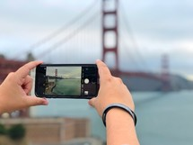 a woman taking a picture of the Golden Gate Bridge with her cellphone