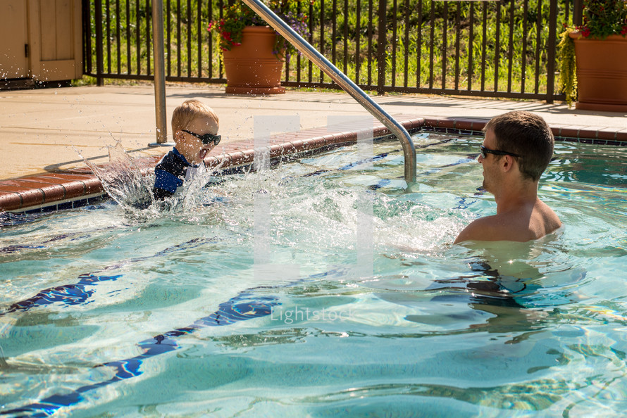 father and son swimming in a pool