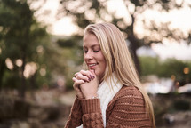 a woman in a sweater with praying hands