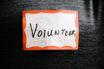 the word volunteer on a name badge