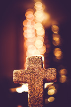 stone cross and bokeh lights