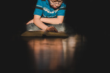 boy reading a Bible on a wood floor
