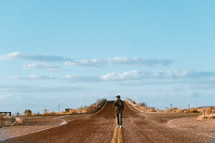 a man walking down the middle of a rural road
