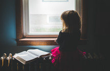 a girl looking out a window and an open Bible