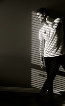 young man posing in sunlight through blinds