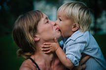 a toddler boy kissing his mother