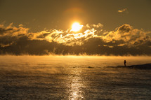 rising steam over ocean water and a man standing on a shore at sunrise
