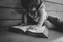 toddler reading a Bible