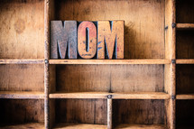 "Wooden letters spelling ""mom"" on a wooden bookshelf."