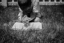 a boy kneeling in the grass reading a Bible God's Word  and praying