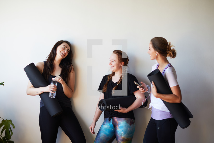 woman with yoga mats in a yoga studio