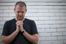 a man with praying hands standing in front of a white brick wall