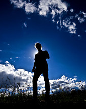 silhouette of a man under a cobalt blue sky
