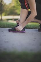 Runner tying shoes on the sidewalk.