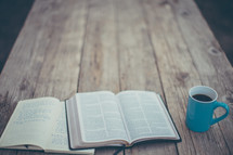 open Bible, journal, and coffee mug on a wood table