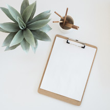 A clipboard with blank paper, cup of pencils, and a succulent plant on a white surface.