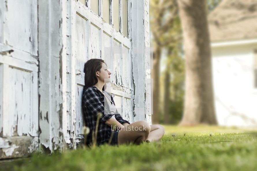 woman sitting in front of an old garage