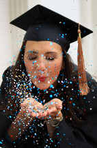 a female graduate blowing confetti