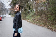a smiling young woman standing in the middle of a road