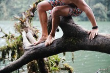 man sitting on a fallen tree hanging over a lake