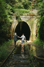 couple walking on old railroad tracks