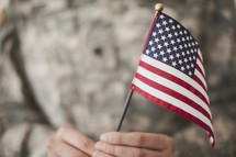 Small American flag held by an army soldier.