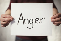 A man holding a piece of paper with the word Anger on it