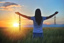 Woman feeling free in a beautiful natural setting, in what field at sunset. Free from chains