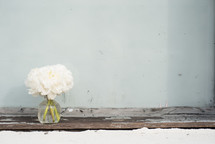 A vase of white flowers on an aged wooden board.