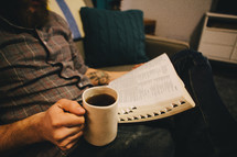 A man reading a Bible and holding a cup of coffee in his living room.